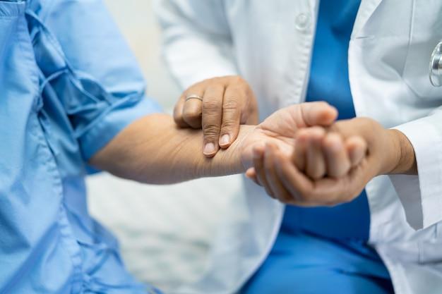 El doctor toma el pulso con el paciente en la sala del hospital de enfermería, concepto médico fuerte y saludable.