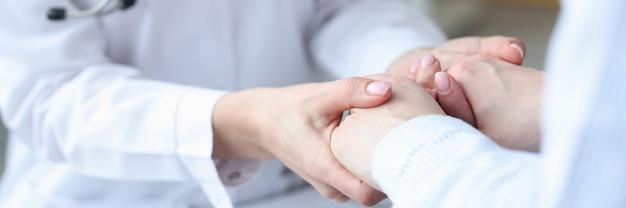 Doctor tomados de la mano del paciente en la clínica closeup concepto de ayuda psicológica