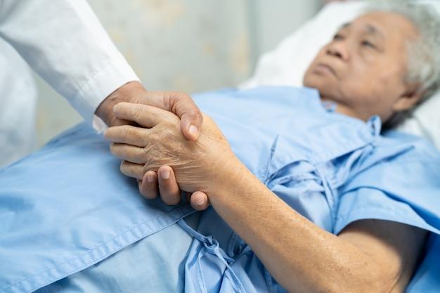 Doctor tomados de la mano paciente mayor asiático de la mujer con amor.
