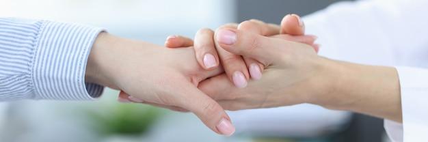 Doctor tomando la mano de los pacientes en la clínica closeup concepto de apoyo psicológico