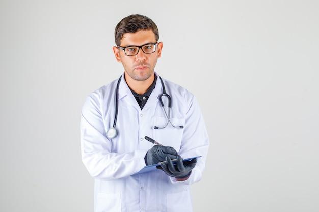 Doctor tomando notas en bata blanca médica