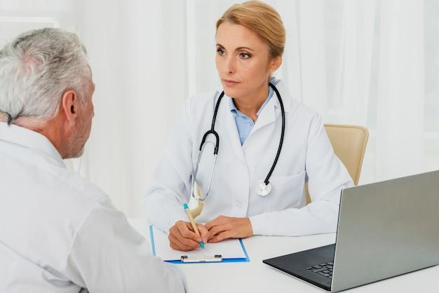 Doctor tomando notas con paciente