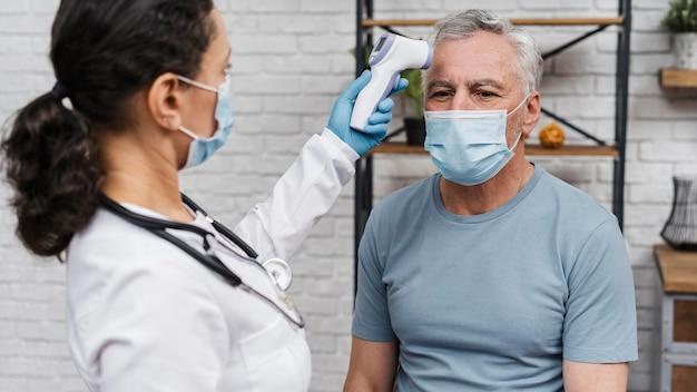 Doctor tomando la temperatura de los pacientes