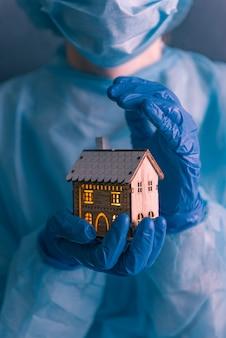 Doctor, un trabajador médico con guantes médicos en sus manos, un abrigo y una máscara en la cara, sostiene en sus manos una pequeña casa con ventanas luminosas.