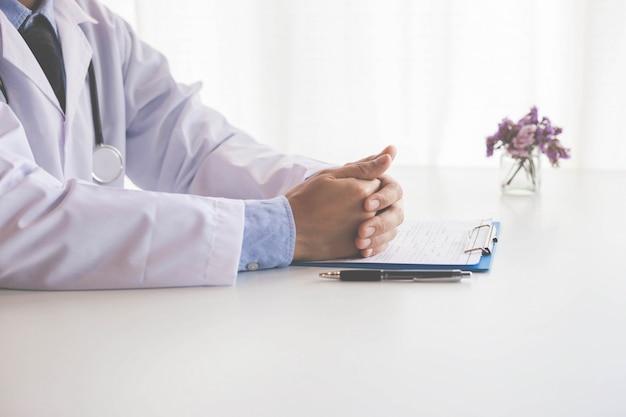 Doctor trabajando con la computadora portátil y escribir en el papeleo. fondo del hospital