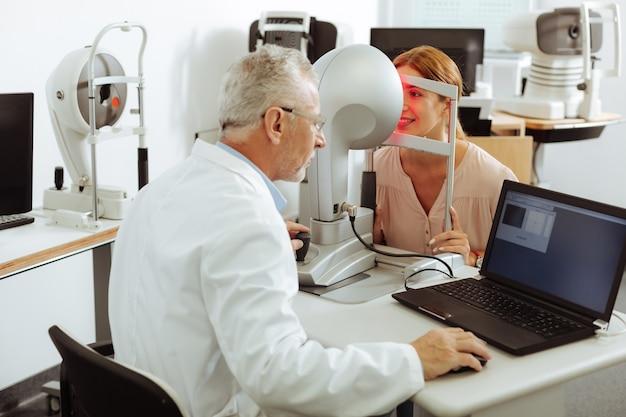 Doctor trabajando duro. oftalmólogo experimentado profesional trabajando duro mientras examina a la mujer