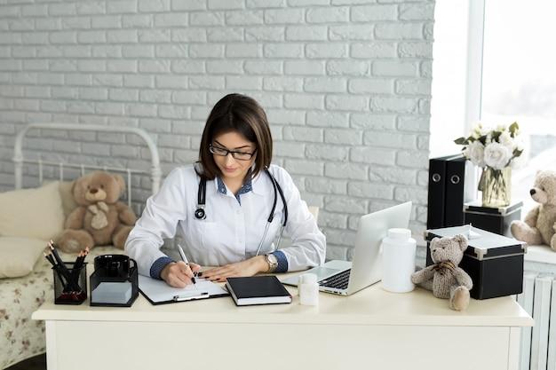 Doctor trabajando con laptop y escribiendo en papeleo