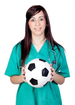 Doctor trigueno atractivo con el balón de fútbol aislado en a sobre el fondo blanco