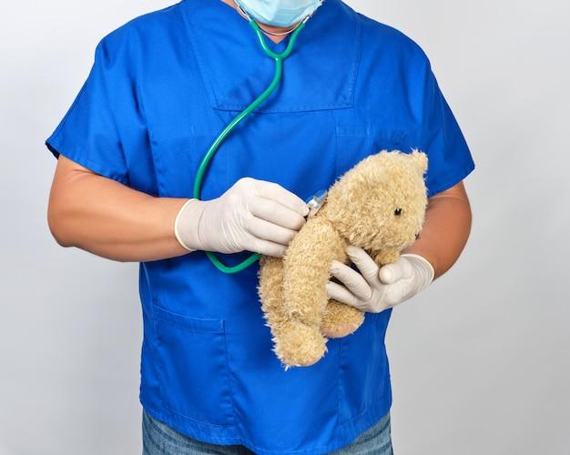 Doctor en uniforme azul y guantes de látex blancos con un oso de peluche marrón