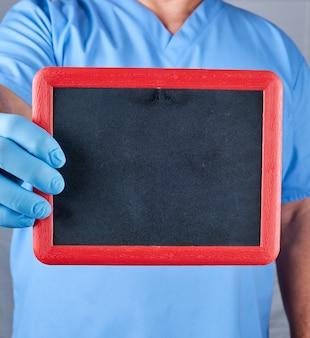 Doctor en uniforme azul y guantes de látex estériles sosteniendo un marco negro en blanco