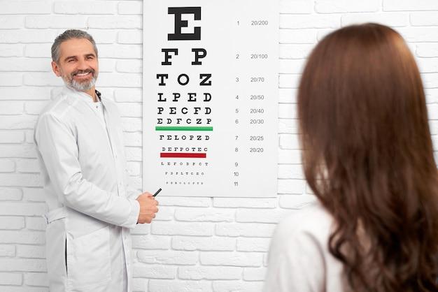 Doctor en el uniforme blanco que se coloca cerca de prueba carta de ojo.