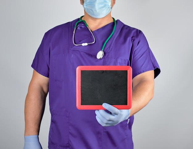 Doctor en uniforme y guantes estériles de látex sosteniendo un marco negro en blanco