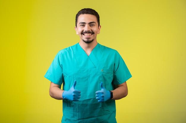 Doctor en uniforme y máscara de mano satisfecho y sonriente, de pie en el medio.