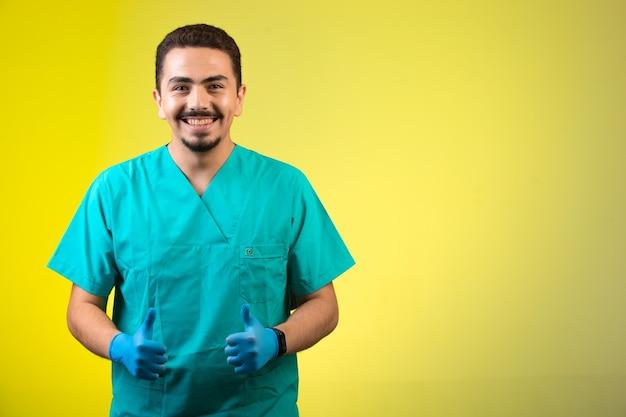 Doctor en uniforme y máscara de mano satisfecho y sonriente.
