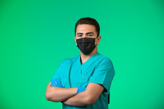Doctor en uniforme verde y mascarilla haciendo posando en posición satisfecha.