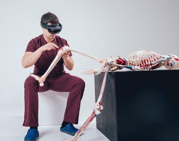 El doctor usa gafas de realidad aumentada para examinar el esqueleto humano