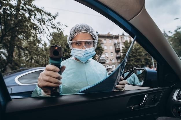 El doctor usa una pistola de termómetro infrarrojo para controlar la temperatura corporal