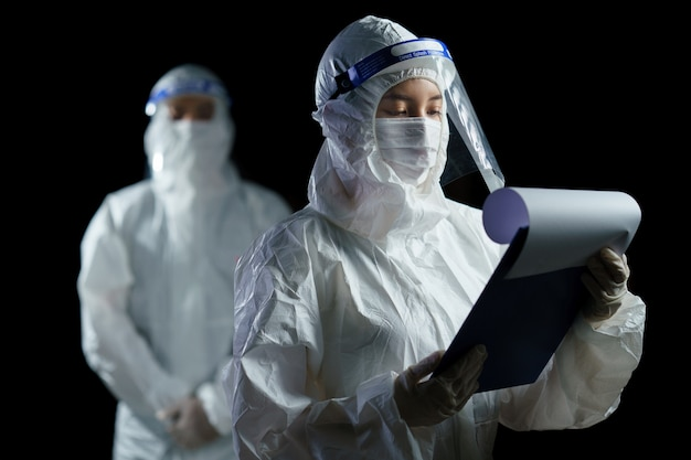 Doctor usando ppe y careta buscando informe de laboratorio de virus corona / covid-19.