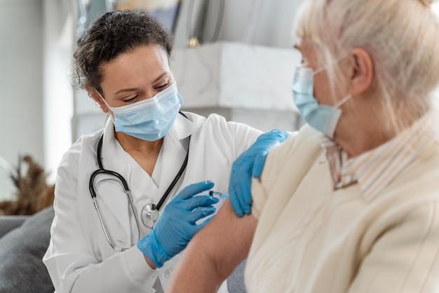 Doctor vacunando a una mujer mayor