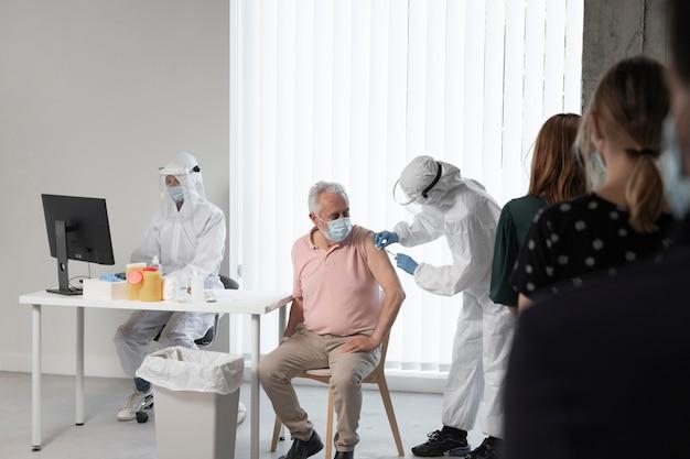Doctor vacunando a un paciente en un centro