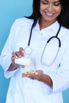 Doctor vistiendo bata blanca y estetoscopio sosteniendo pastillas
