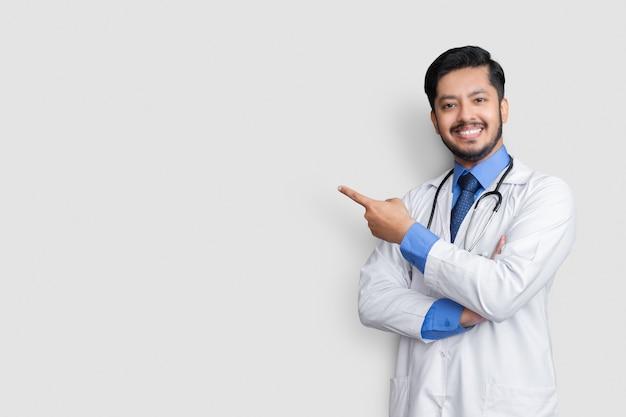 Doctor vistiendo uniforme sonriendo mientras presenta y apunta aislado en la pared azul con espacio de copia
