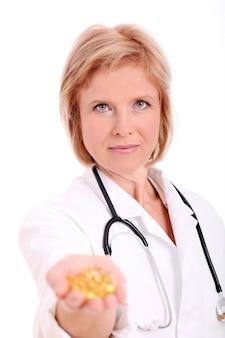 Doctora adulta con pastillas en su mano sobre fondo blanco.