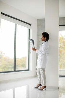 Doctora afroamericana vistiendo bata blanca con estetoscopio de pie junto a la ventana en la oficina y mirando la imagen de rayos x