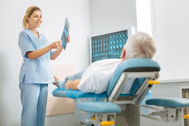 Doctora. alegre mujer bonita inteligente sosteniendo una imagen de rayos x y hablando con su paciente mientras lo trata