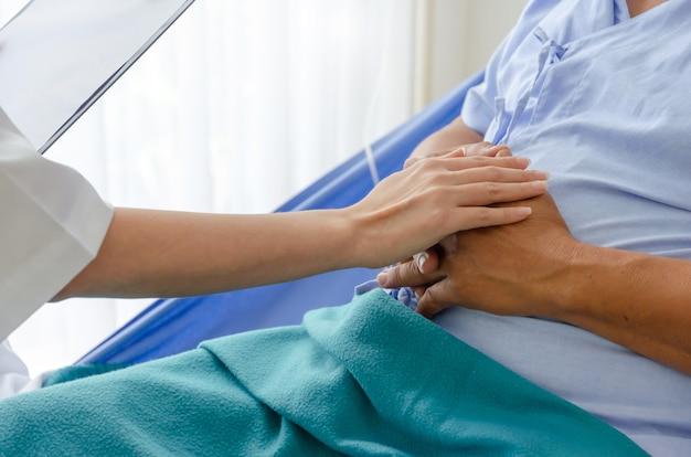 Doctora amigable hablando y manteniendo la mano del paciente anciano acostado en la cama en el hospital para alentar, brote de virus, cuarentena, recuperación, ancianos, médicos, concepto de atención médica