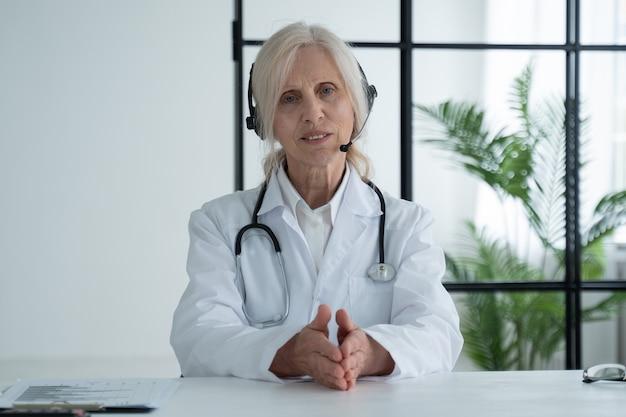 Doctora anciana con una bata médica blanca mirando a la cámara y hablando con auriculares sentado en una oficina de hospital