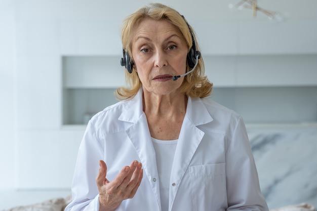 Una doctora anciana con experiencia que habla a la cámara y brinda asesoramiento médico en línea en un