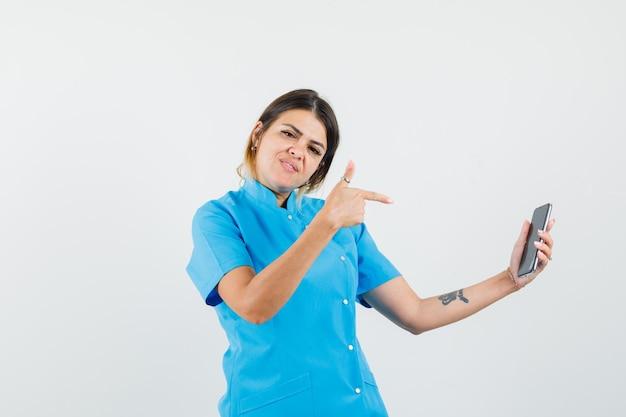 Doctora apuntando al teléfono móvil en uniforme azul y mirando confiado