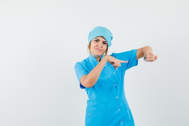 Doctora apuntando a su reloj en la muñeca en uniforme azul y mirando con cuidado