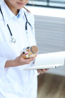 Doctora asiática, mujer especialista con cuaderno y pastillas