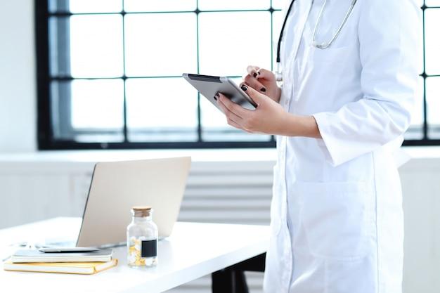 Doctora asiática, mujer especialista con laptop y pastillas
