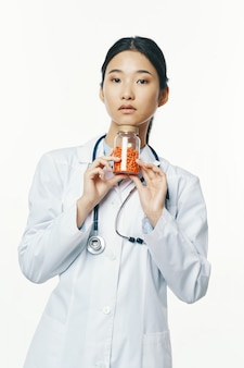 Doctora asiática con pastillas de naranja