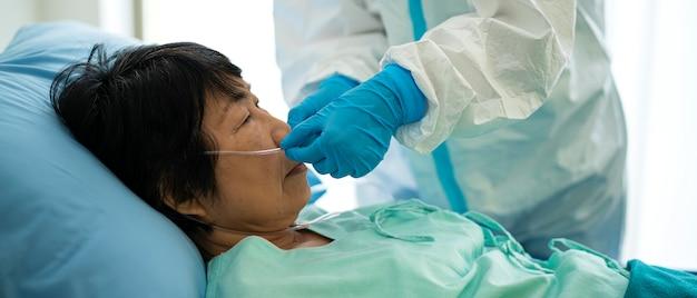 La doctora asiática y el personal médico con traje médico ppe usan máscara de ventilador para el virus corona o el paciente covid-19 en el área de cuarentena en el hospital. brote de virus, máscara médica o concepto de cuarentena