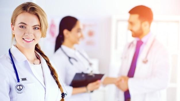 Doctora atractiva frente a grupo médico, personal médico revisando registros médicos en el fondo