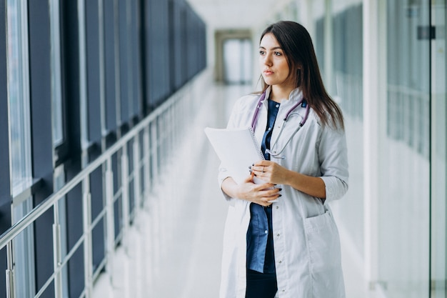 Doctora atractiva de pie con documentos en el hospital