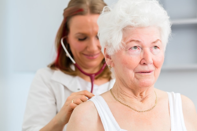 Doctora ausculta el aliento y los pulmones del pensionista con estetoscopio en cirugía