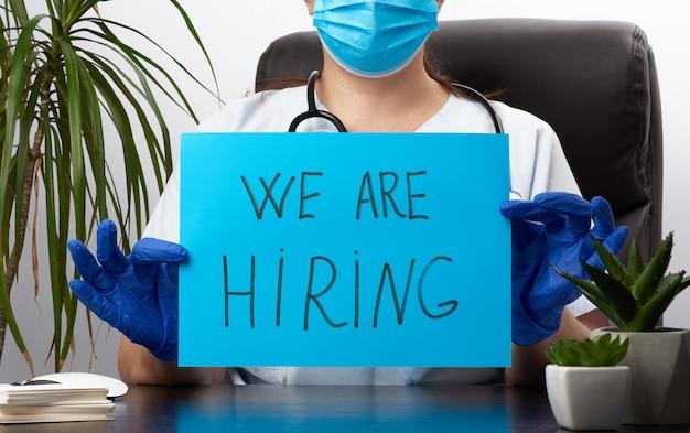 Doctora en una bata blanca, guantes médicos estériles sostiene un cartel con la inscripción que estamos contratando, concepto de personal