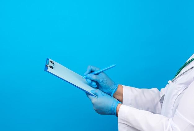Doctora en una bata blanca, guantes médicos de goma azul sostiene una carpeta para papeles y con su mano derecha escribe en una hoja