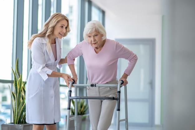 Doctora en una bata de laboratorio alentando a un paciente mayor con andador rodante