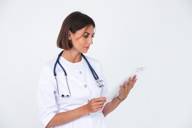 Doctora en bata de laboratorio en blanco aislado, sonrisa confiada mantenga papel blanco en blanco