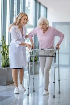 Doctora en una bata de laboratorio caminando con un paciente mayor con andador rodante
