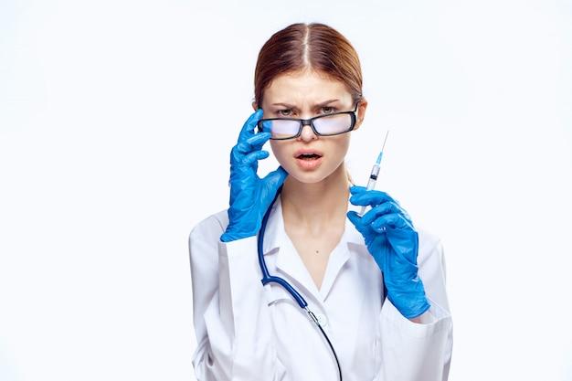 Doctora en una bata médica, terapeuta con gafas en un espacio aislado blanco