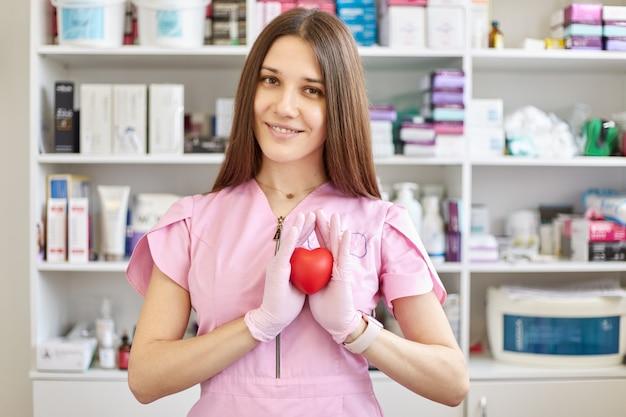 Doctora con bata rosa y guantes de látex