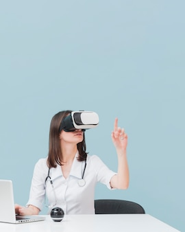 Doctora con casco de realidad virtual con espacio de copia