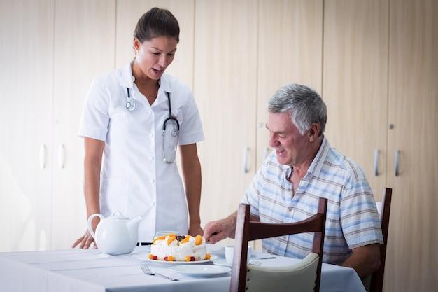Doctora celebración seniors hombre cumpleaños en sala de estar